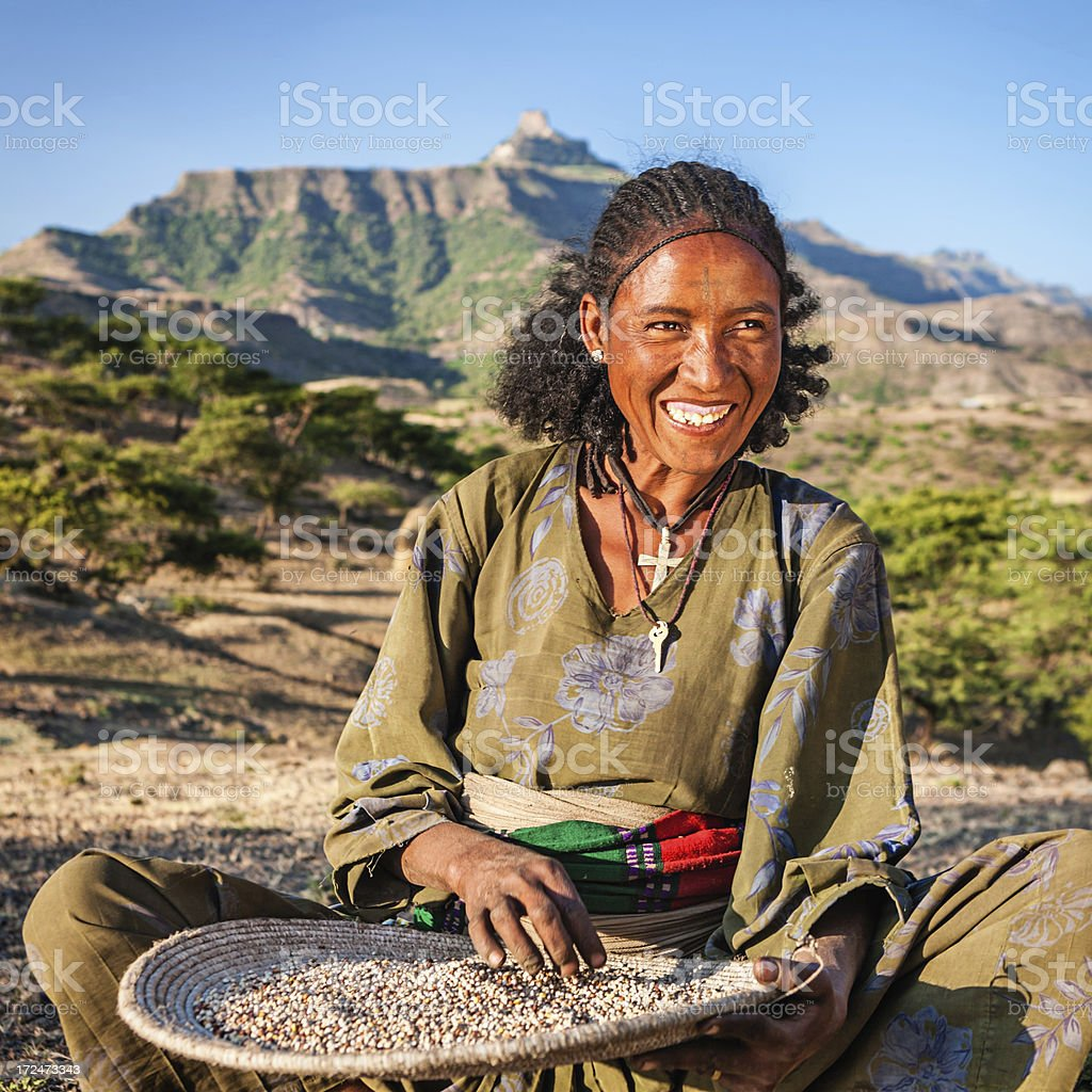 African woman is sifting the sorghum, East Africa royalty-free stock photo