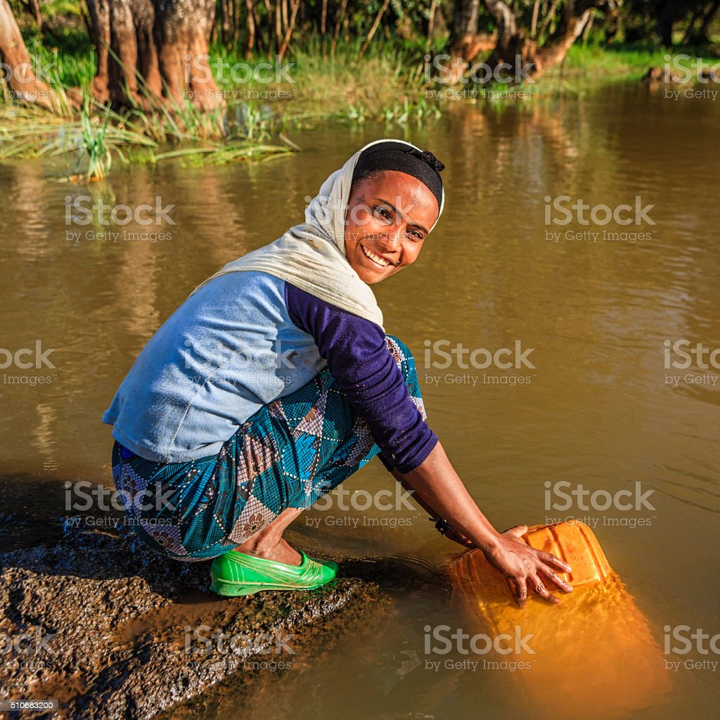 African woman is taking water from the river, Ethiopia, Africa stock photo