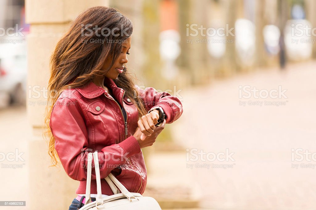 african woman looking at watch stock photo