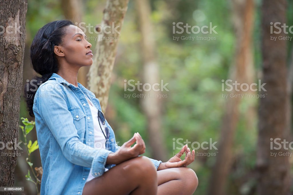 African woman meditating in forest. stock photo