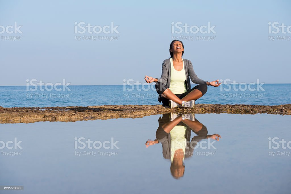 African woman meditating on seashore. stock photo