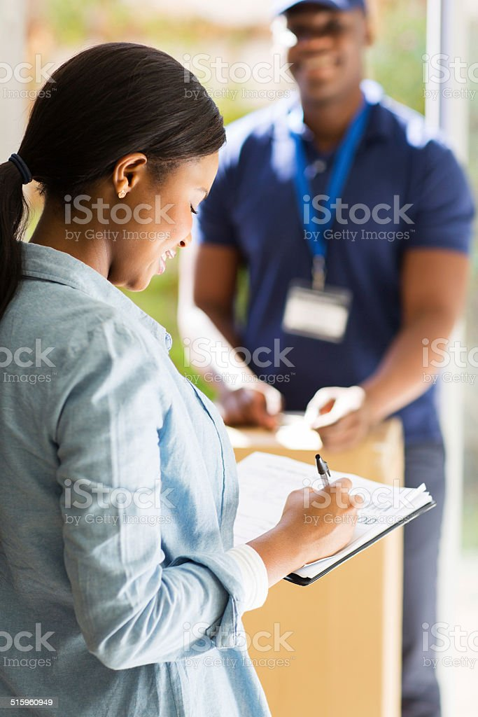 african woman receiving post and signing document stock photo