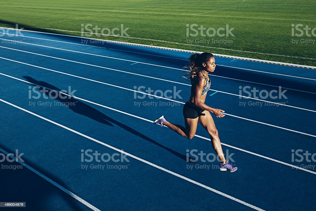 African woman running on racetrack stock photo