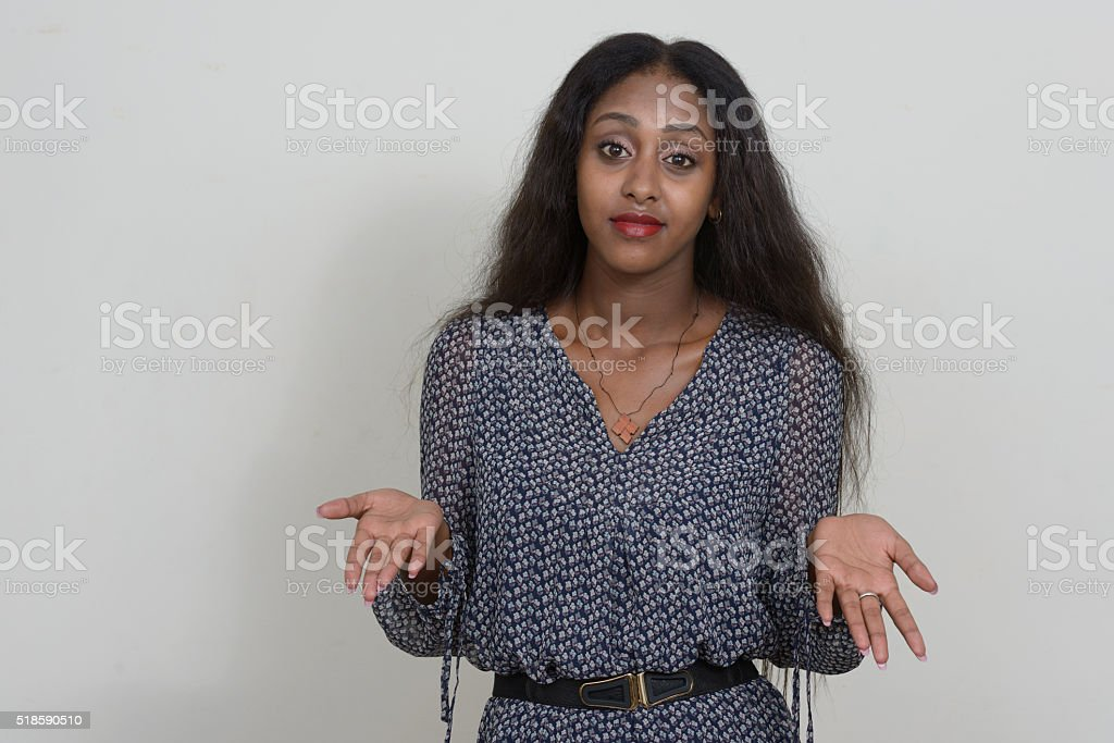 African woman shrugging shoulders stock photo