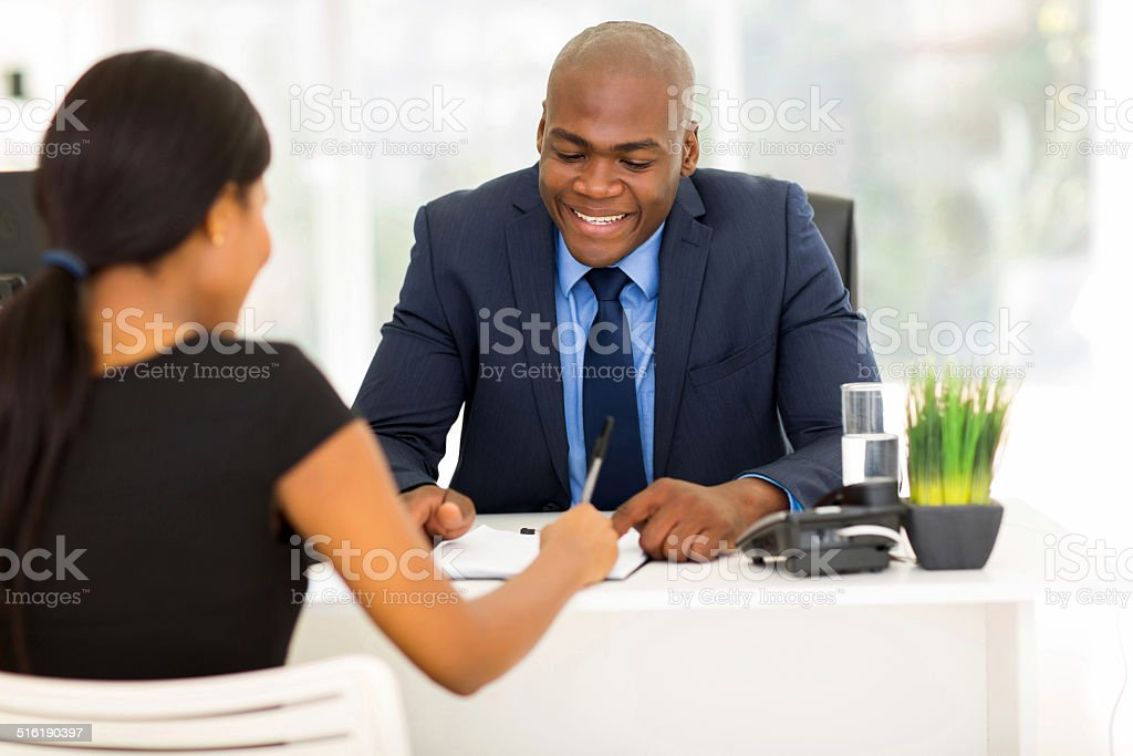 african woman signing employment contract stock photo