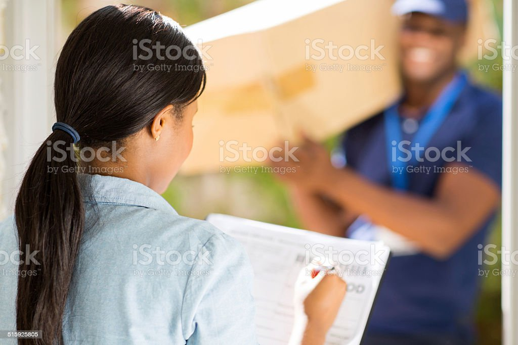 african woman signing receiving paper stock photo