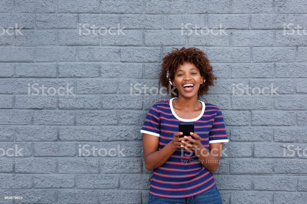 Portrait of african woman smiling and holding cell phone