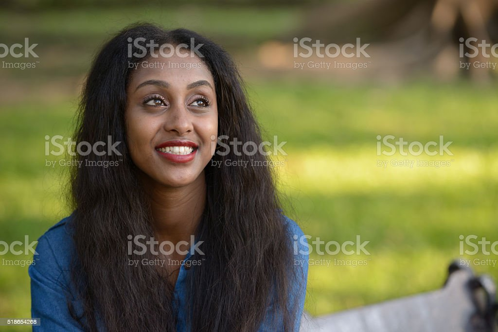 African woman smiling outdoors at park stock photo