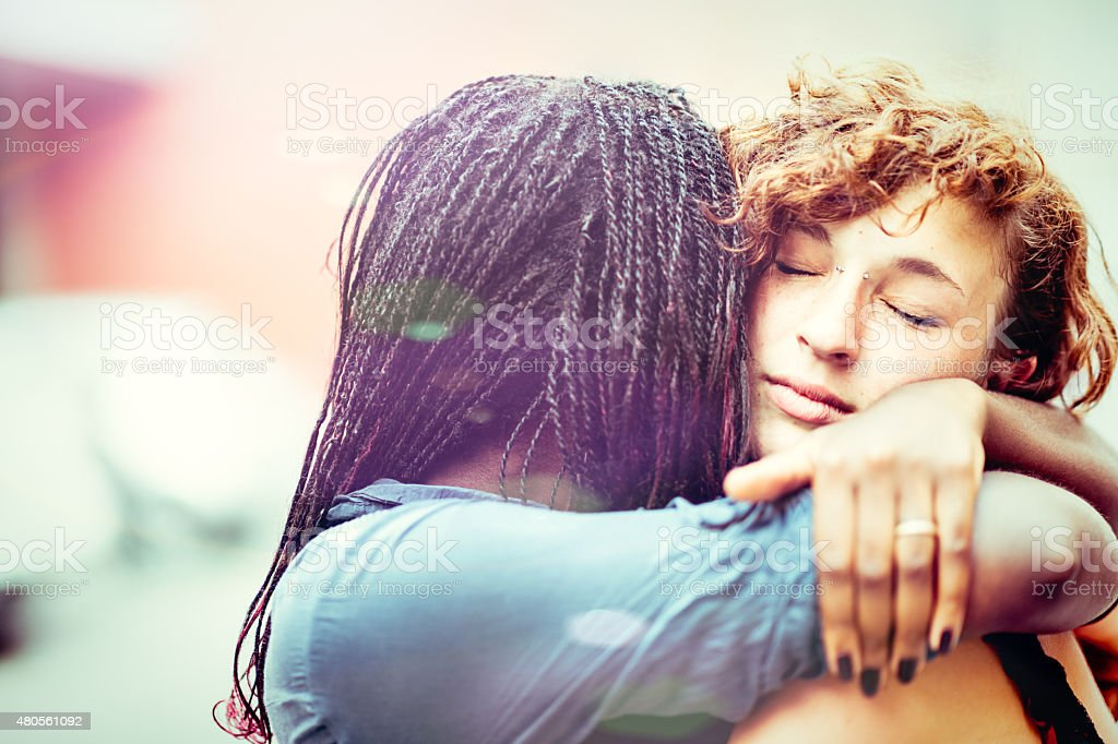 African woman supporting her Caucasian girlfriend stock photo