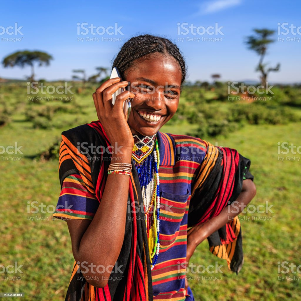 African woman from Borana tribe using mobile phone, village in...