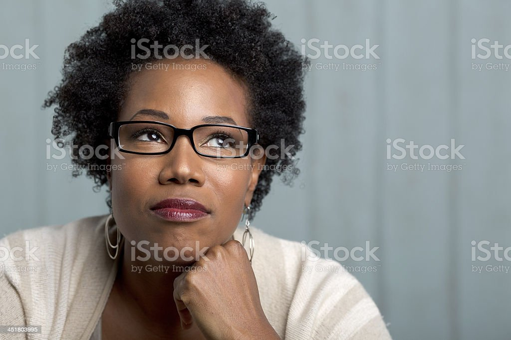 african woman wearing glasses with a hand on chin stock photo