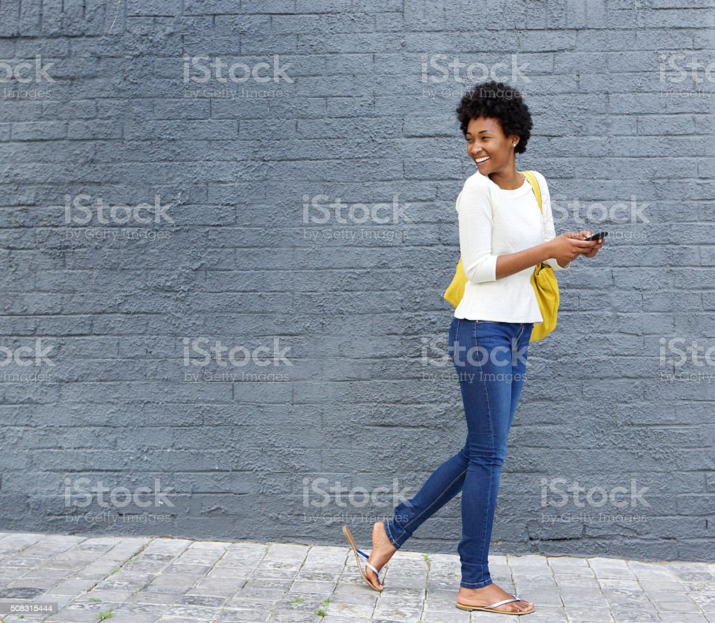 African woman with a cell phone looking over her shoulder stock photo