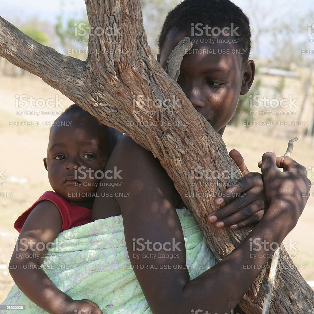 African woman with child in the shade of a tree royalty-free stock photo