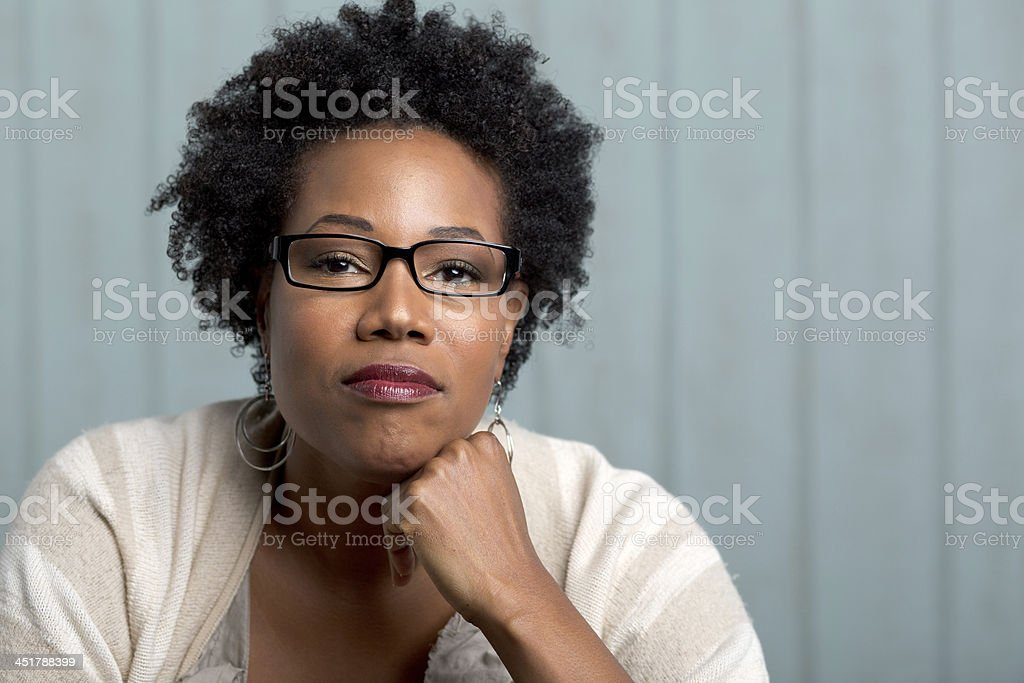 african woman with hands on chin staring at camera stock photo