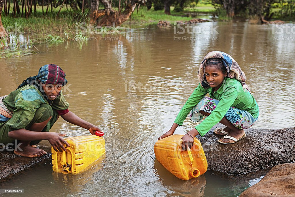 African women are taking water from the river, Ethiopia, Africa stock photo