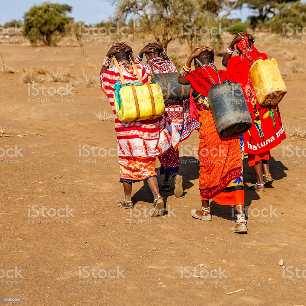 African women from Maasai tribe carrying water, Kenya, East Africa stock photo