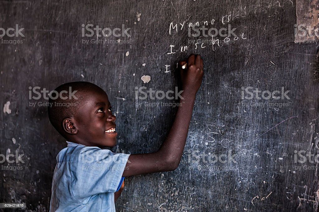 African young boy is learning English language, orphanage in Kenya stock photo