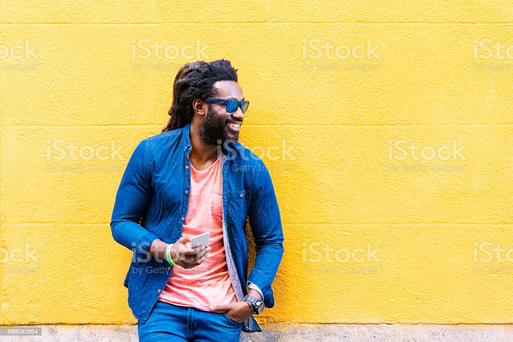 African Young Man Using Mobile In The Street. stock photo