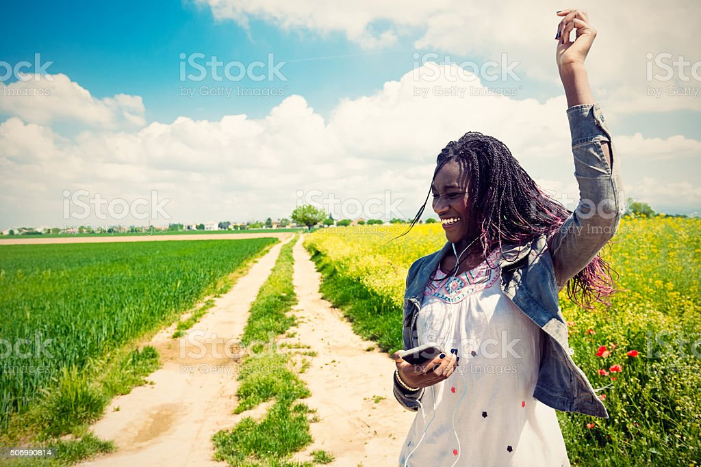 African young woman listening to music in coutryside stock photo