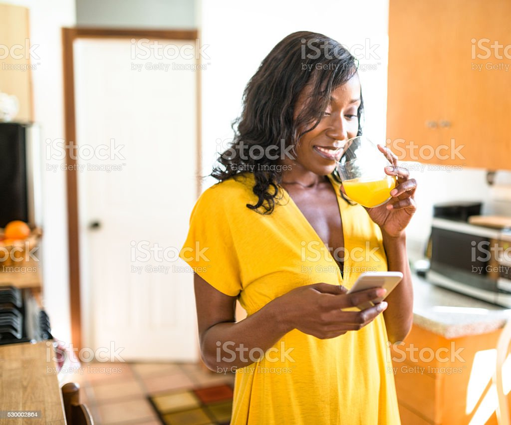african young woman smiling drinking orange juice stock photo