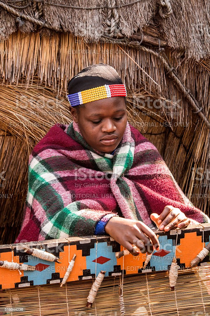 African Zulu woman in ethnic clothes weaves straw carpet. stock photo