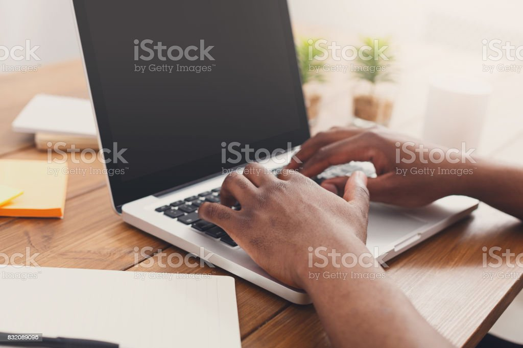 African-american businessman in office type on laptop stock photo