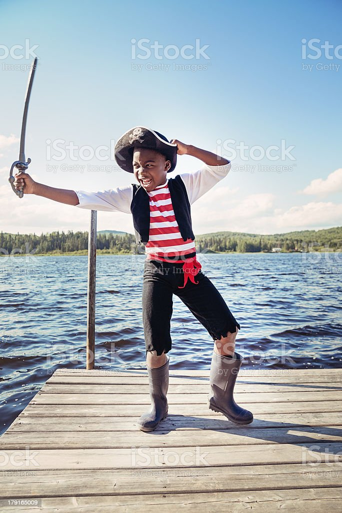 African-american child dressed as pirate on a lake. royalty-free stock photo