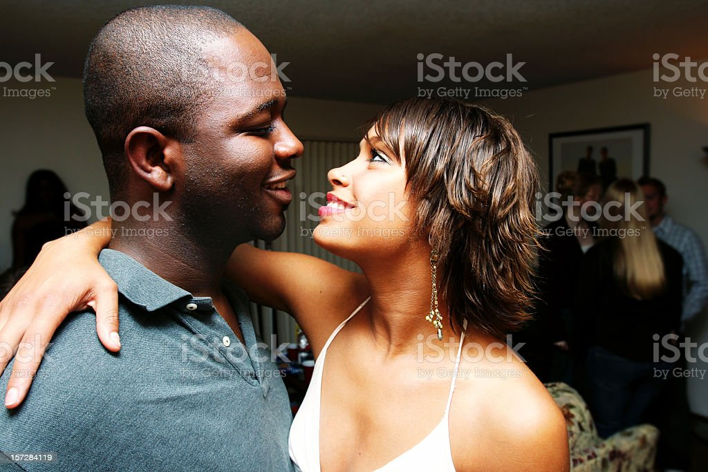 African-American couple smiling at one another at a party stock photo