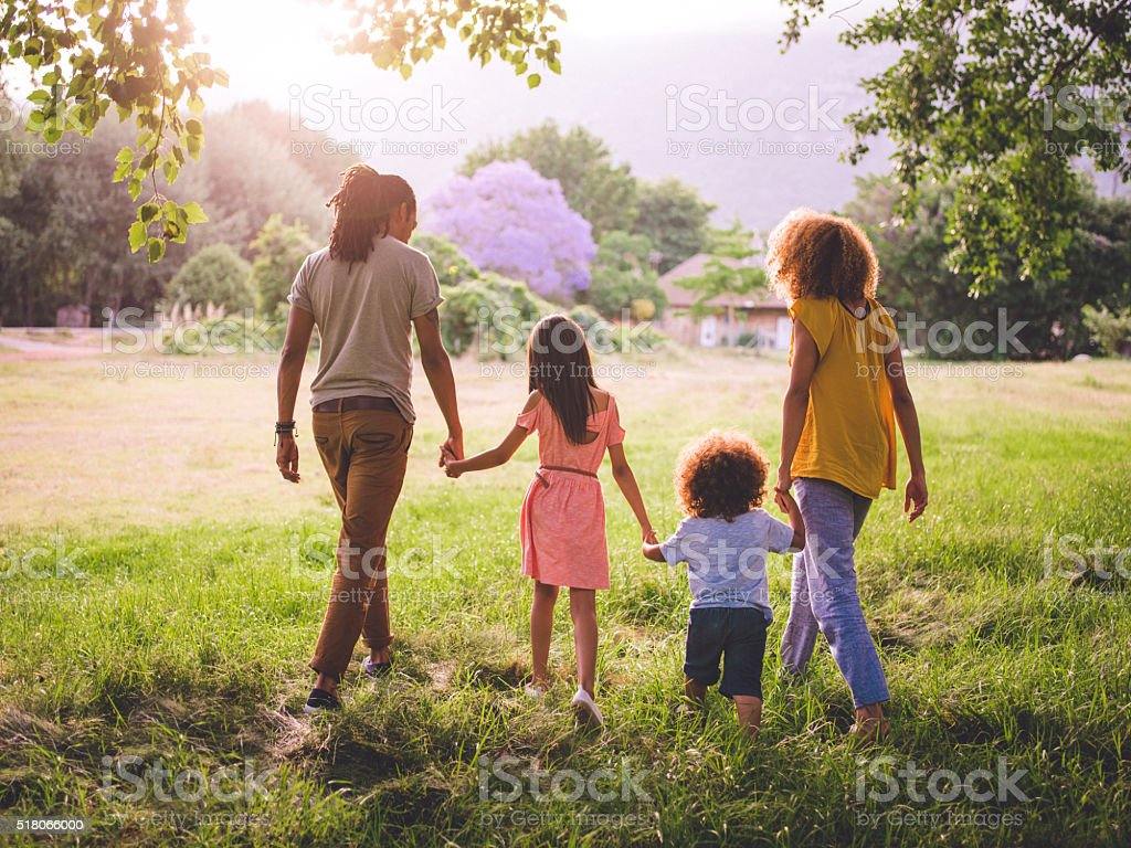 African-american family walking in a gorgeous picturesque park while...