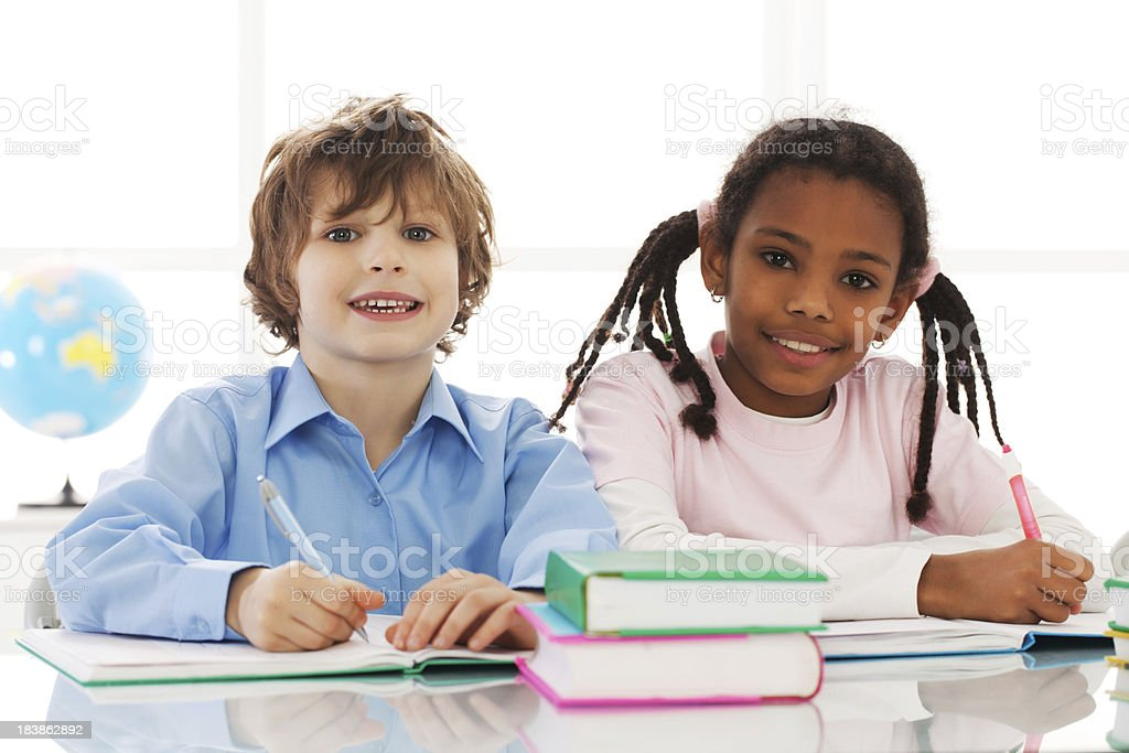 African-American girl and Caucasian boy are doing homework. royalty-free stock photo