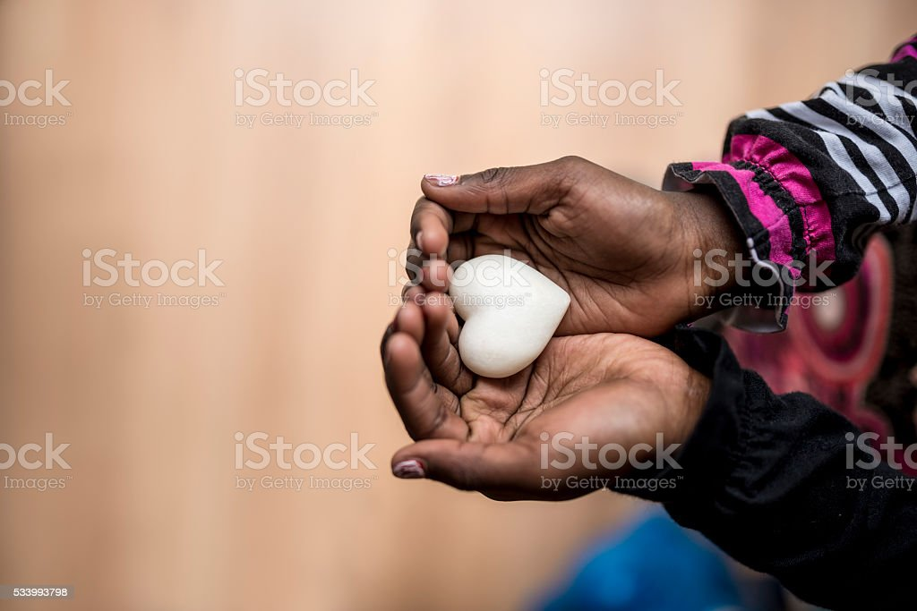 African-American girl holding a marble made heart shape stock photo