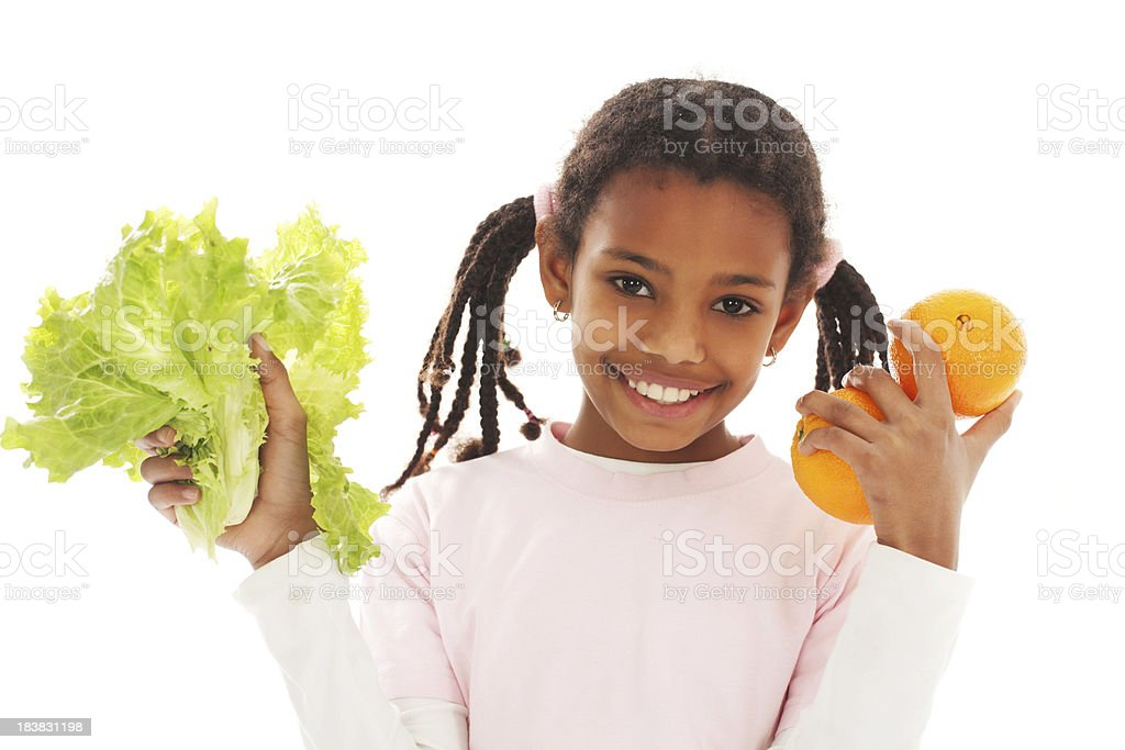 African-American girl holding vegetables and fruit. royalty-free stock photo