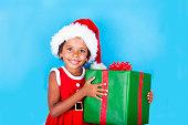 African-american little girl holding big Christmas gift box.