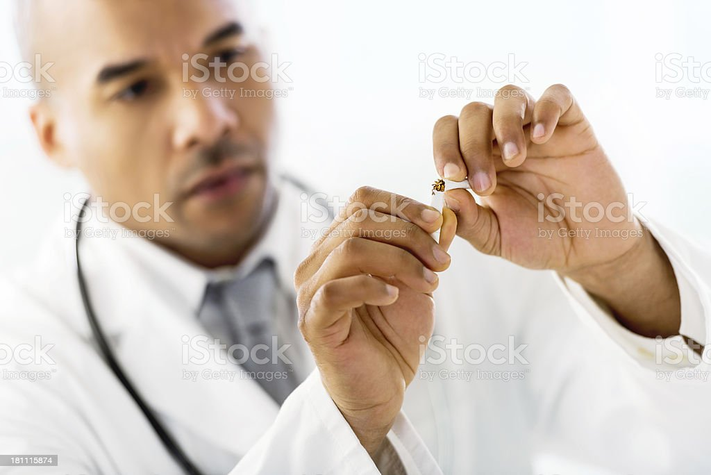 African-American male doctor breaking a cigarette. royalty-free stock photo