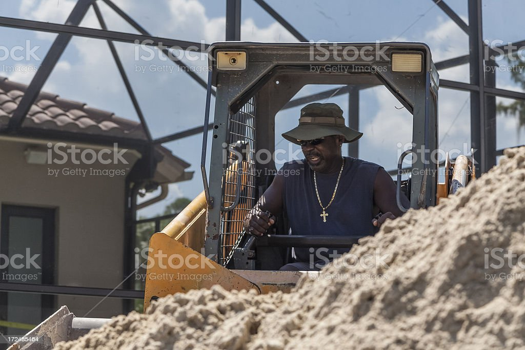 African-American Man Operating Bobcat on Construction Site royalty-free stock photo