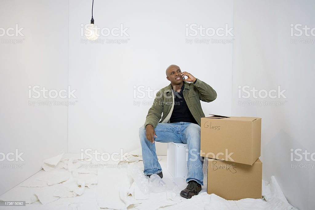 African-American man packing boxes makes a call on his cell royalty-free stock photo