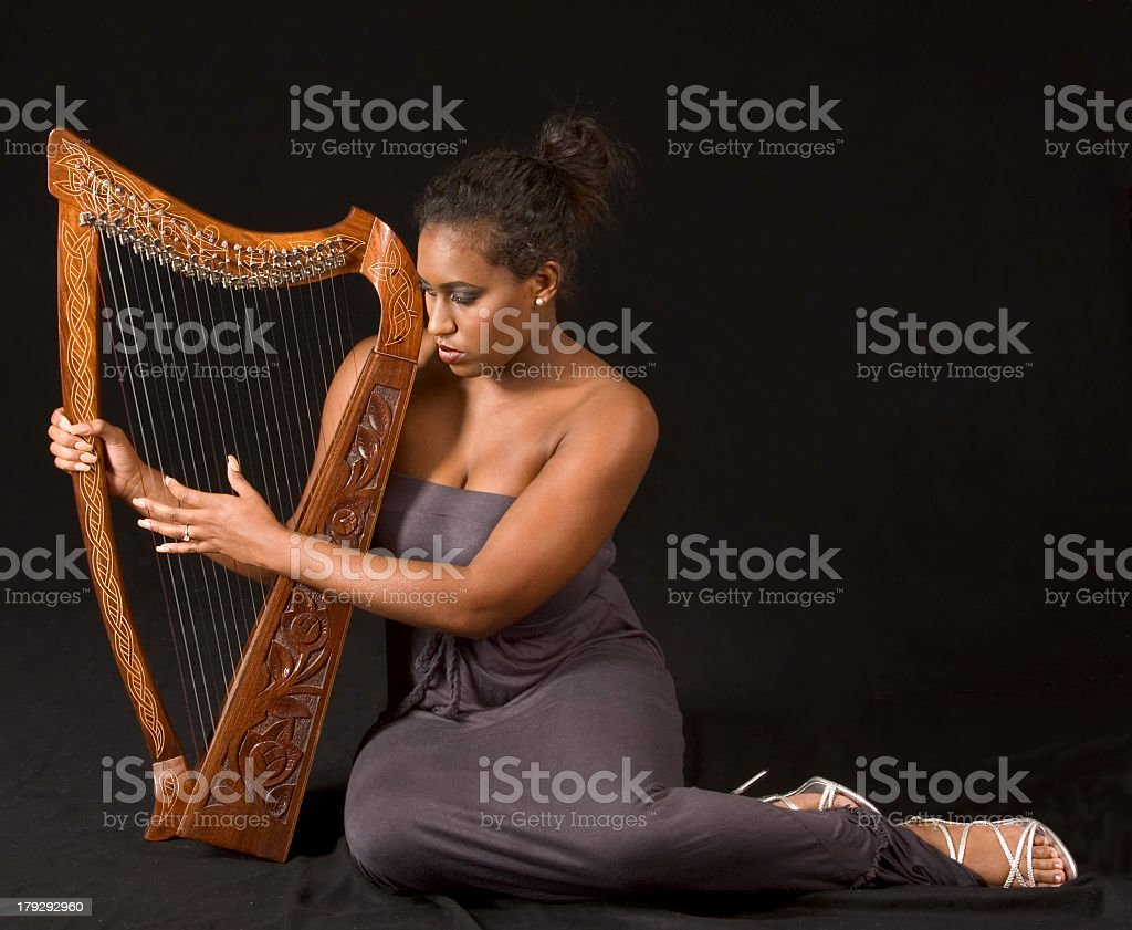 African-American woman in gray sitting and playing harp stock photo