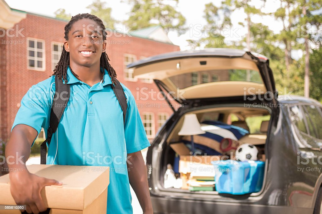 African-descent boy moves into college dorm. stock photo