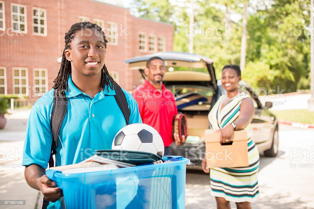 African-descent boy moves into college. Packed car, family.  School campus. stock photo