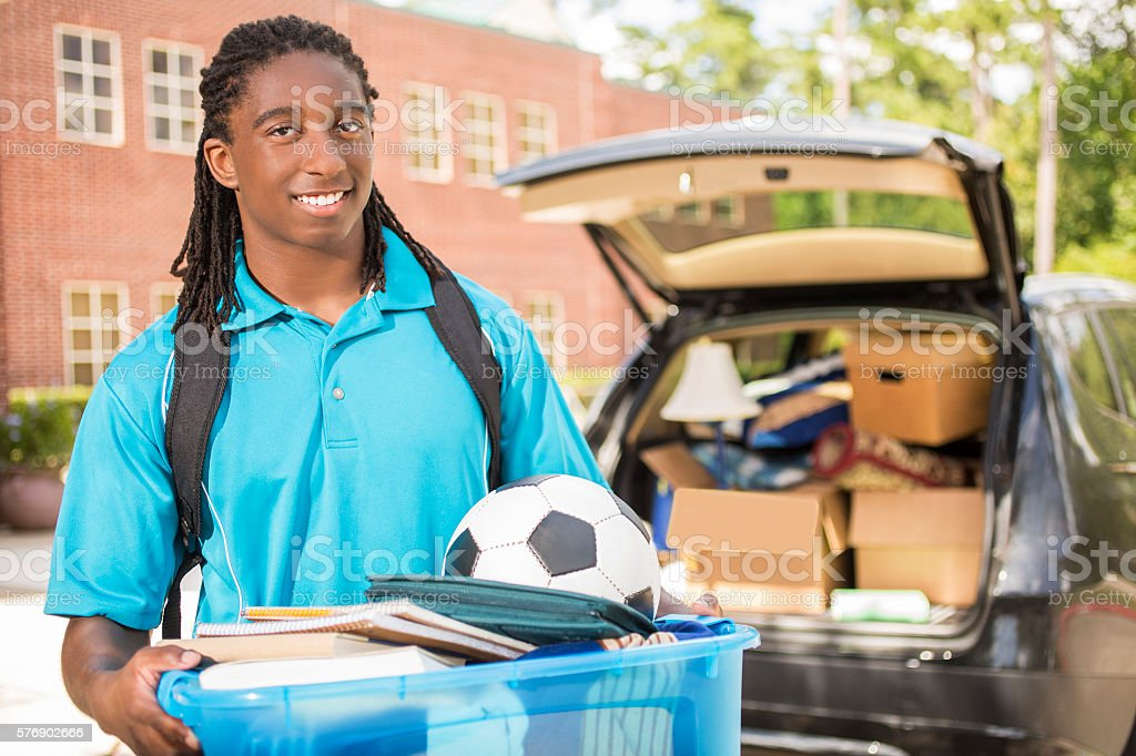 African-descent boy moves into college. Packed car.  School campus. stock photo