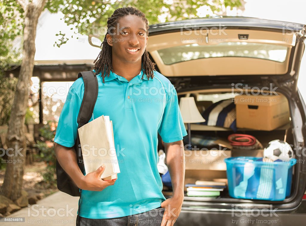 African-descent boy moves off to college.  Packed car, home. stock photo