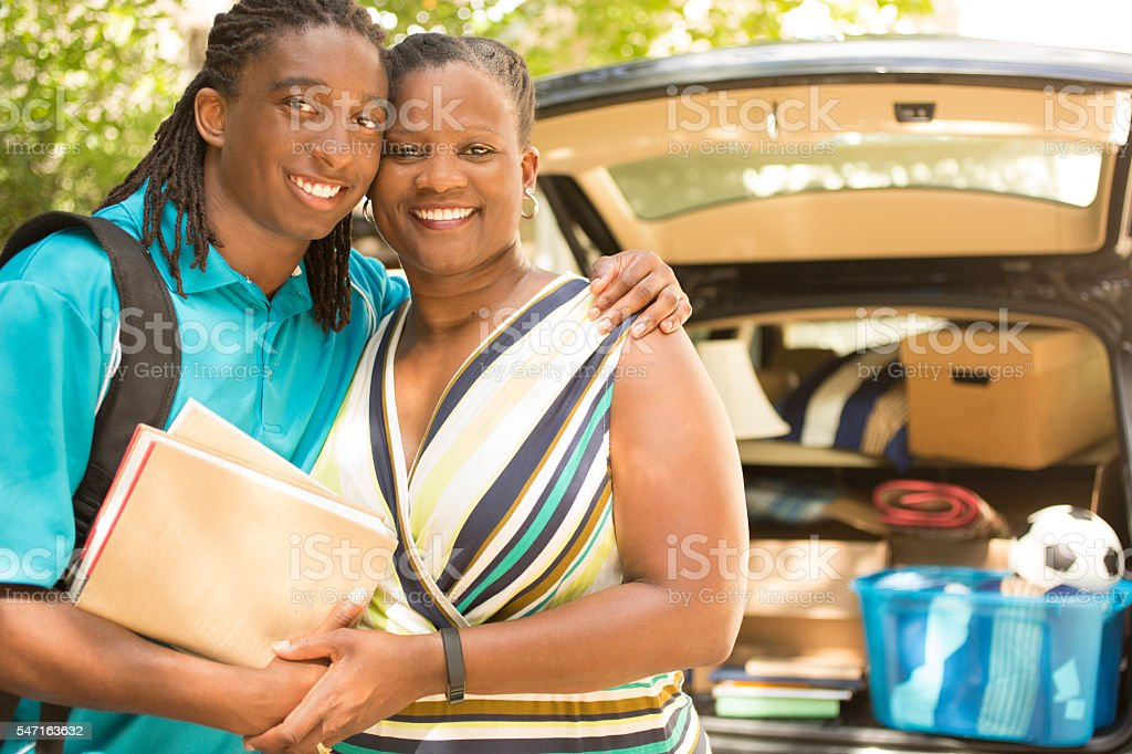 African-descent boy moves off to college.  Packed car, mom.  Hug. stock photo