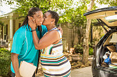 African-descent boy moves off to college.  Packed car, mom. Kiss.