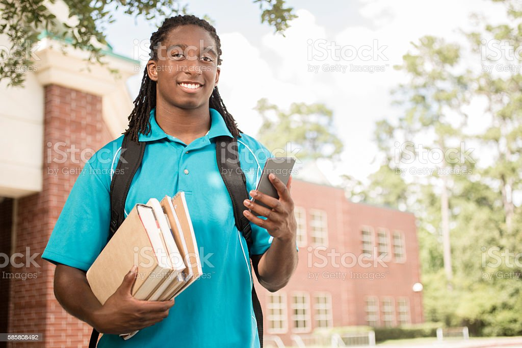 African-descent boy on college school campus using cell phone. stock photo