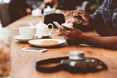 Afro amercian man using smart phone in coffee shop