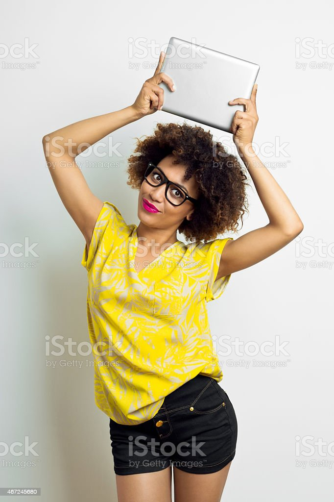 Afro Amercian Young Woman holding digital tablet above her head stock photo