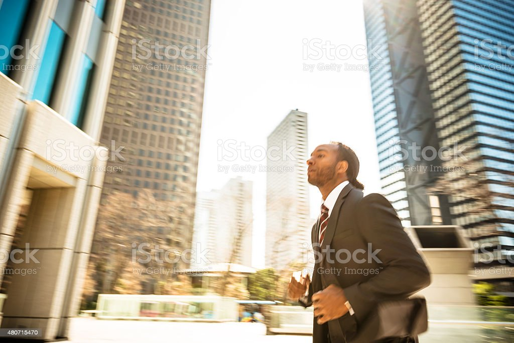 Afro american Business running on rush on the city stock photo