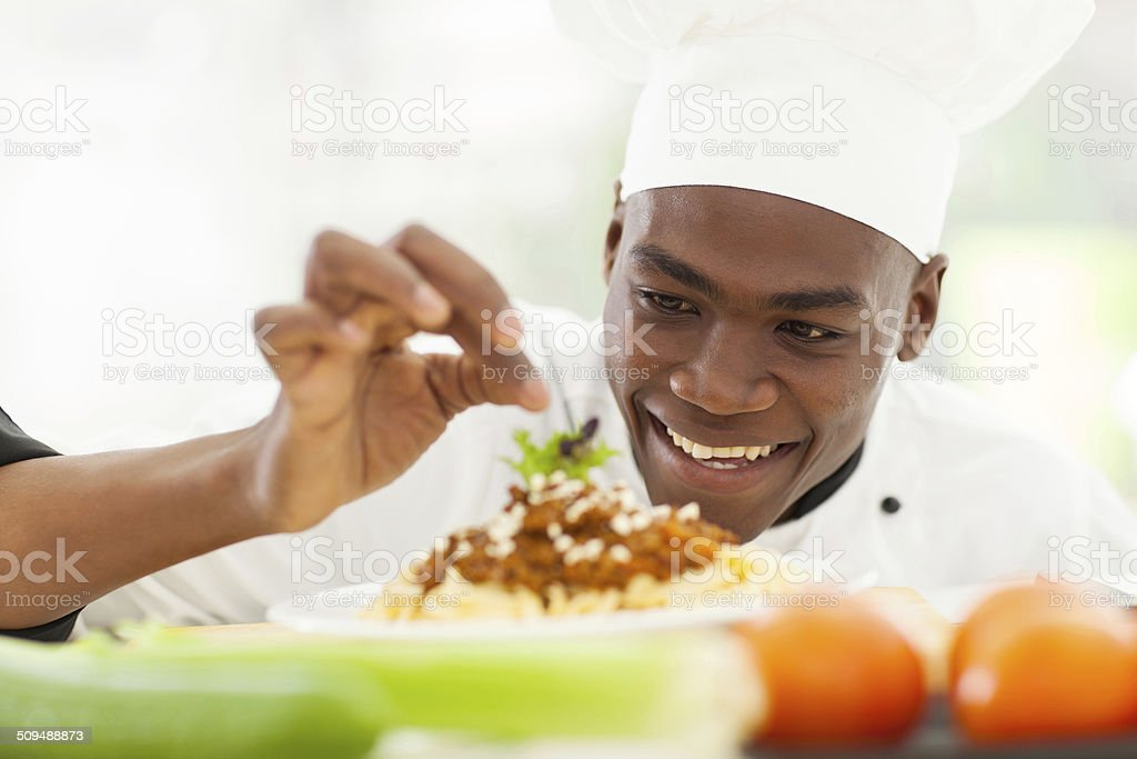 Afro American chef in restaurant kitchen garnishing pasta dish stock photo