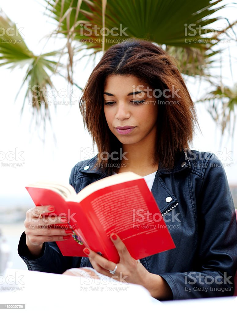 Afro american female reading a book outdoors stock photo