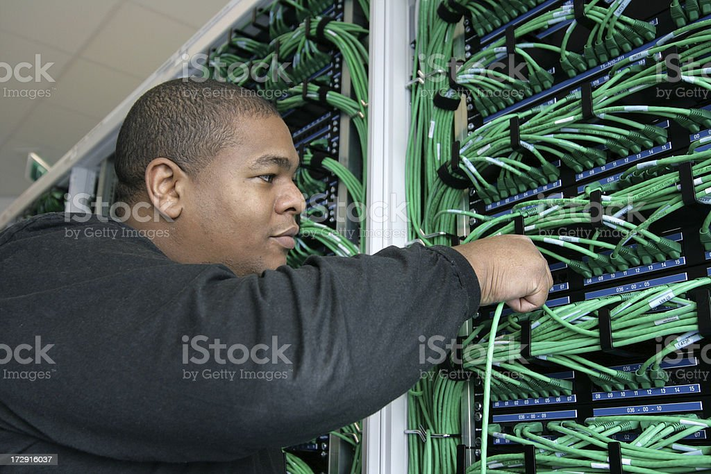 Afro american It worker plugs in a Cable royalty-free stock photo